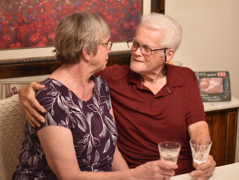 man hugs woman while sharing champagne